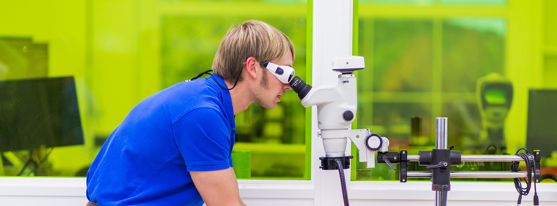 Cadence employee looking through microscope